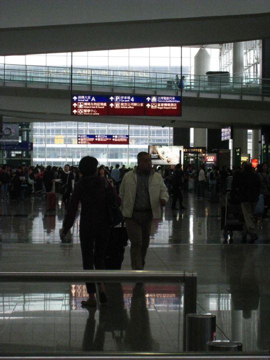 香港国際空港で藤村と待ち合わせ。金子に気付かず、さっそうと歩く藤村。