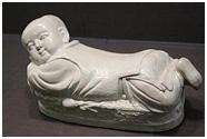 「白磁嬰児型枕」 ・この枕は日用品として使われていました ・赤ん坊は衣服の上に模様の入った錦織のベストを着ています