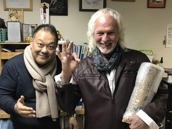内藤貞夫先生から贈られたお酒を手に微笑むスティーブホールマーク氏